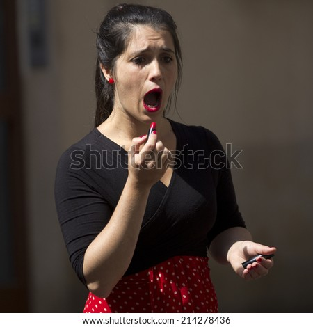 AURILLAC, FRANCE-AUGUST 22: a spanish actress puts on her lipstick in the street as part of the  Aurillac International Street Theater Festival, on august 22, 2014, in Aurillac,France.  - stock photo