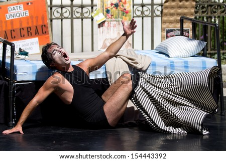 AURILLAC, FRANCE - AUGUST 21: an actor plays near a bed in the street as part of the Aurillac International Street Theater Festival, Company Les hommes papillon,on august 21, 2013, in Aurillac,France  - stock photo