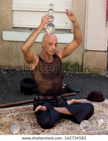 AURILLAC, FRANCE - AUGUST 23: Portrait of a street performer, named Jyoti, playing with balls as part of the Aurillac International Street Theater Festival, on august 23, 2013, in Aurillac,France  - stock photo