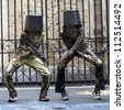 AURILLAC, FRANCE - AUGUST 23: Two dancers, with a bucket on the head, move as Michael Jackson, Aurillac International Street Theater Festival, show Vachement, on august 23, 2012, in Aurillac,France. - stock photo