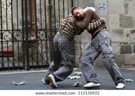 AURILLAC, FRANCE - AUGUST 24: two masked dancers fight in the street as part of the Aurillac International Street Theater Festival,show by the Company Idem,on august 24, 2012, in Aurillac,France. - stock photo