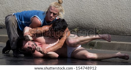 AURILLAC, FRANCE - AUGUST 22: two semi-naked men fight on the ground as part of the Aurillac International Street Theater Festival, Company Monsieur Linea,on august 22, 2013, in Aurillac,France  - stock photo