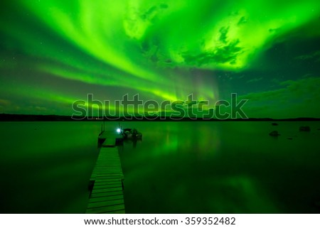 Aurora Borealis at Lake - Strong bands of aurora borealis bright up the starry night sky and a lake.  - stock photo