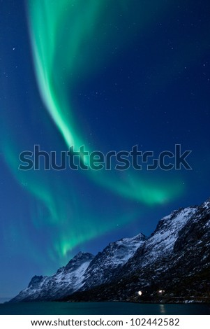 Aurora Borealis in Norway above a fjord - stock photo