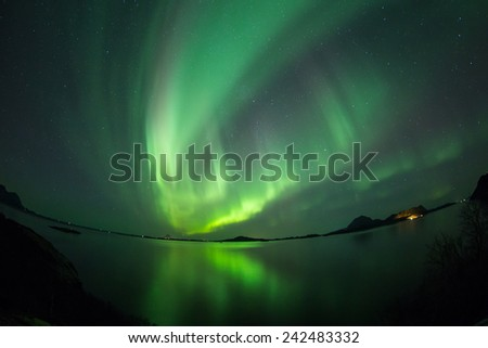 Aurora Borealis (Northern lights) Over coastal sea with reflection and fish-eye lens - stock photo