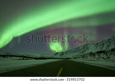 Aurora Borealis Northern Lights over empty road and snow capped mountains - stock photo