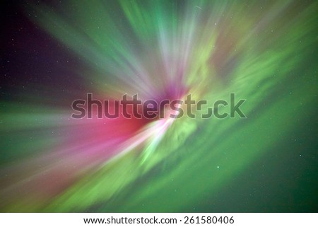 Aurora borealis or northern lights above the lake in the winter with vibrant colors and starry sky on the background. - stock photo