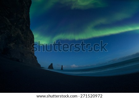 Aurora borealis or the northern lights or Northern light at Reynisdrangar Iceland - stock photo