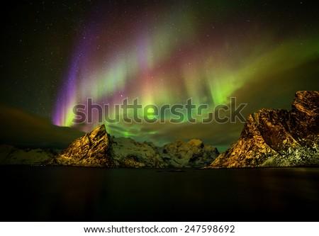 Aurora borealis (Polar lights) over the mountains in the North of Europe - Reine, Lofoten islands, Norway - stock photo