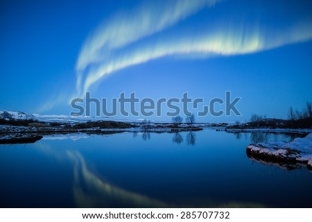 Aurora northern lights mirror reflection in mountain lake at sunset, Thingvellir, Iceland - stock photo