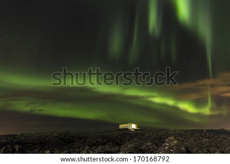 Aurora with observatory in larva field at the Blue Lagoon Iceland - stock photo