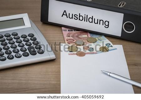 Ausbildung (German education) written on a binder on a desk with euro money calculator blank sheet and pen - stock photo