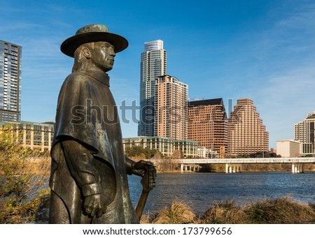 AUSTIN, TEXAS - JANUARY 5: Stevie Ray Vaughan statue in front of downtown Austin and the Colorado River from Auditorium Shores on January 5, 2014 in Austin, Texas - stock photo