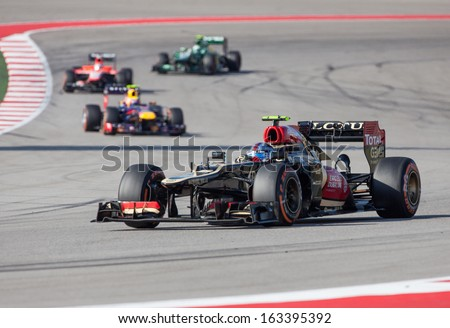 AUSTIN, TEXAS - NOVEMBER 17.  Romain Grosjean of Team Lotus rounding Turn 13 ahead of Mark Webber of Red Bull during the Formula 1 United States Grand Prix on November 17, 2013 in Austin, Texas.  - stock photo