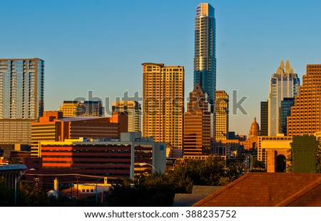 Austin Texas Skyline on Town Lake or Lady Bird Lake or Colorado river with Reflections of the Evening Sunset Creating Glowing Golden Orange Red Shades off the Skyscrapers Downtown from South Congress - stock photo