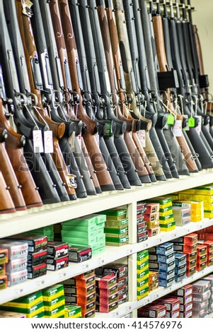 AUSTIN, TX - NOV 7: Rack of shotguns and boxes of ammunition for sale at a gun store in Austin, Texas in November 7, 2015. - stock photo