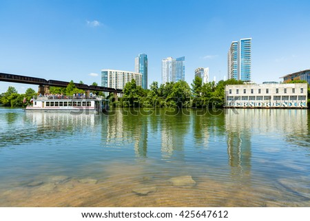 Austin, TX USA - April 14, 2016: Skyline view of downtown Austin along the Colorado River with tour boat cruising by.