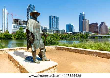 Austin, TX USA - April 14, 2016: Skyline view of the downtown district along the Colorado River with the statue of the late Stevie Ray Vaughan.