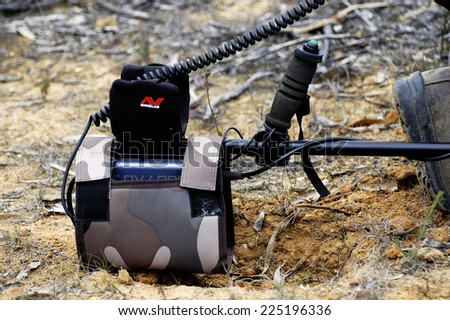 AUSTRALIA - APRIL 24: Detail of a metal detector placed on the floor while the gold miner digs where the machine has given the signal, April 24, 2007 - stock photo