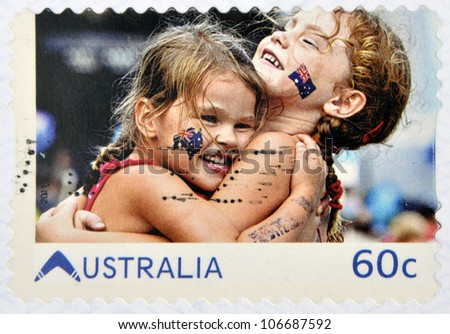 AUSTRALIA - CIRCA 2011: A stamp printed in australia shows embrace of friendship between two girls with the Australian flag in the face, circa 2011 - stock photo