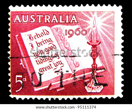 "AUSTRALIA - CIRCA 1960: A stamp printed in Australia shows image of a Candle and Open Bible with text ""I bring you good tidings of great joy"", Luke 2-10, from the series ""Christmas Issue"", circa 1960"