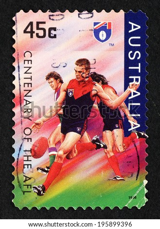AUSTRALIA - CIRCA 1996: Postage stamp printed in Australia with image of Aussie Rules Football player to commemorate the centenary of the Australian Football League. - stock photo