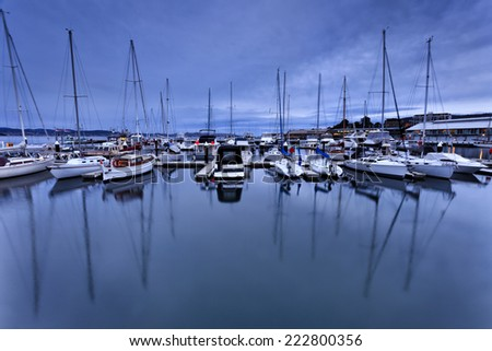 Australia Hobart city marina docked at sea and river cove at sunset panoramic view on yachts with masts reflecting in still water - stock photo