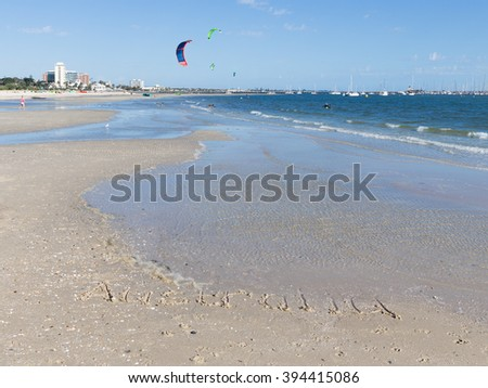Australia inscription on the sand with shells on a large beautiful Australian beach, and unrecognizable people go kite surfing, and bright sails flying over blue sea with small waves, Australia - stock photo