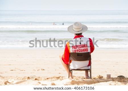 Australia Lifeguard sitting on surveillance chair, front of the ocean. - stock photo