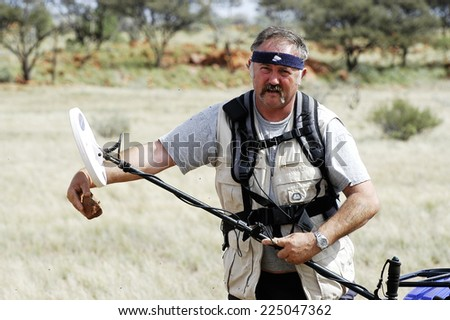 AUSTRALIA - MAY 6: Gold miner in the Australian outback looking to see if a piece of quartz containing gold,  may 6, 2007. - stock photo