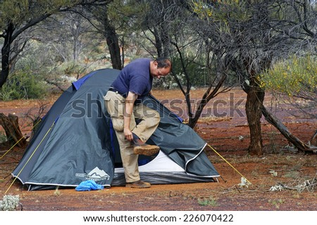 AUSTRALIA - MAY 16 : Hiker in front of his tent in the morning upon waking in the Australian outback near to continue his journey, May 16, 2007.