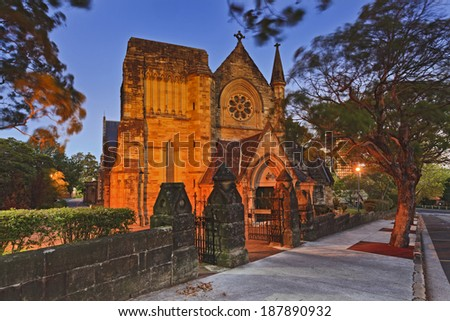 Australia North Sydney anglican church at sunset illuminated with lights front door and facade tower entrance behind the stone wall ancient architecture