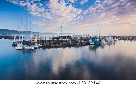 australia protected bay still water sunrise time fishing boats at piers around lighthouse industrial fleet nautical business - stock photo