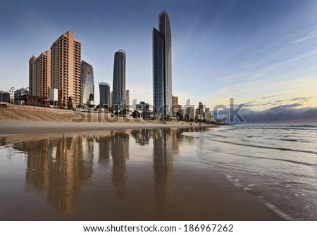AUstralia Queensland SUrfers Paradise cold coast landmark skyscrapers growing from the sea shore reflecting in the beach send after tide wave at sunrise - stock photo