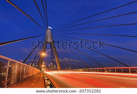 Australia Sydney ANZAC bridge sunset view with blurred vehicle headlights and cables over head - stock photo