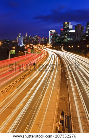 Australia Sydney Cahill expressway motorway vertical view at sunset with blurred vehicle headlights towards city CBD skyscrapers - stock photo