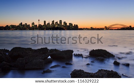 australia sydney CBD cityscape view over harbour at sunset with orange sky skyscrapers, bridge and blurred water - stock photo