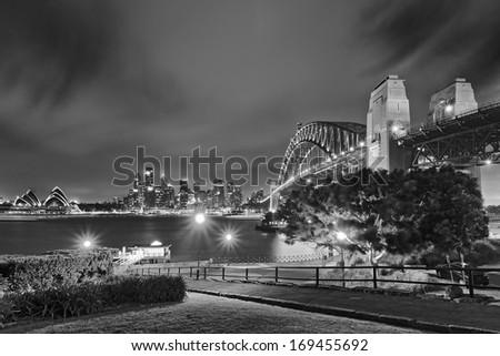 Australia Sydney city CBD and harbour bridge landmarks view from Milsons Point at sunset black white - stock photo