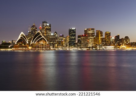 Australia Sydney city CBD landmarks view over harbour at sunset with illumination and blurred lights reflecting in still water - stock photo