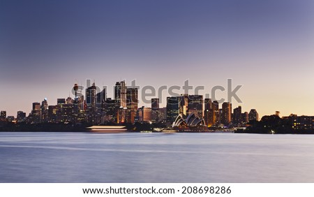 Australia Sydney city CBD panoramic view at sunset across sydney harbour waters blurred waves illuminated landmarks - stock photo