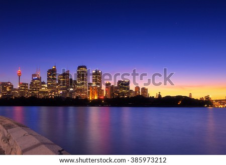 Australia Sydney city CBD view from Mrs Macquarie's Chair over harbour waters at sunset highly illuminated buildings and houses reflecting lights in blurred water - stock photo
