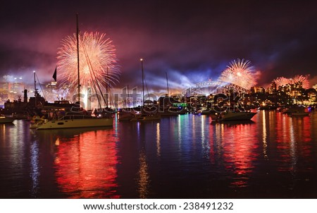 Australia Sydney city fireworks over CBD landmarks harbour bridge, skyscrapers and fleet of yachts and boats anchored in still waters under red celebration fire balls and laser show - stock photo