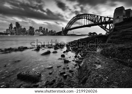 australia sydney city landmarks harbor bridge and CBD at sunset with blurred clouds low tide wet sea bottom rocks - stock photo