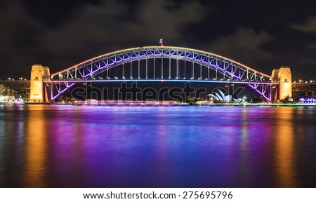 Australia Sydney Harbour Bridge side view of illuminated arch after sunset with bright reflection of the lights in blurred water - stock photo