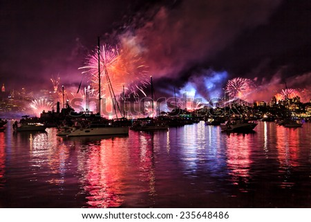 Australia Sydney Harbour waters with boats, yachts and people watching spectacular NAVY fireworks and New Year Eve over Sydney city CBD and harbour bridge - stock photo