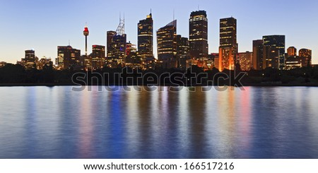 australia sydney panoramic view on city CBD skyscrapers and office towers over harbour with illuminated lights reflected in still water at sunset - stock photo