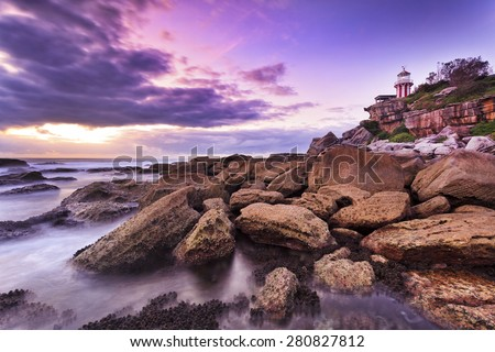 Australia Sydney's South Head Hornby lighthouse from sea level at sunrise with bright sun behind the clouds and wet sandstone rocks in foreground at low tide - stock photo