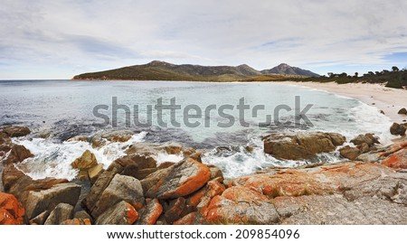 australia tasmania freycinet national park wineglass bay and beach with famous red rocks panoramic view over surf sunny day nobody on the sand - stock photo