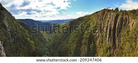 australia tasmania mt Victoria national park eucalyptus trees valley between rocks of mountain range with waterfall and distant farm land - stock photo
