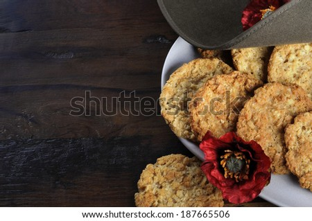 Australian army slouch hat and traditional Anzac biscuits on dark recycled wood with remembrance red poppy for Anzac Day or Remembrance Armistice Day, with copy space. - stock photo